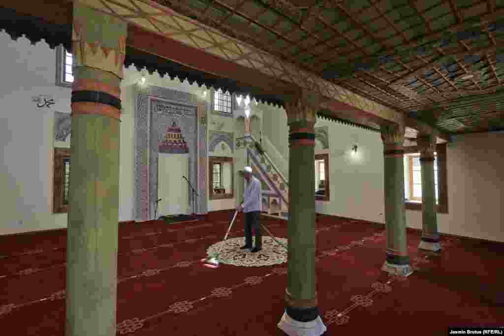 A man vacuums the carpet in the Bascarsija mosque.