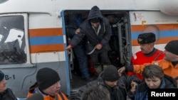 Сотрудники МЧС помогают выжившим морякам затонувшего траулера по их прибытии в Магадан