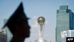 Человек в фуражке у монумента «Байтерек» в Астане.