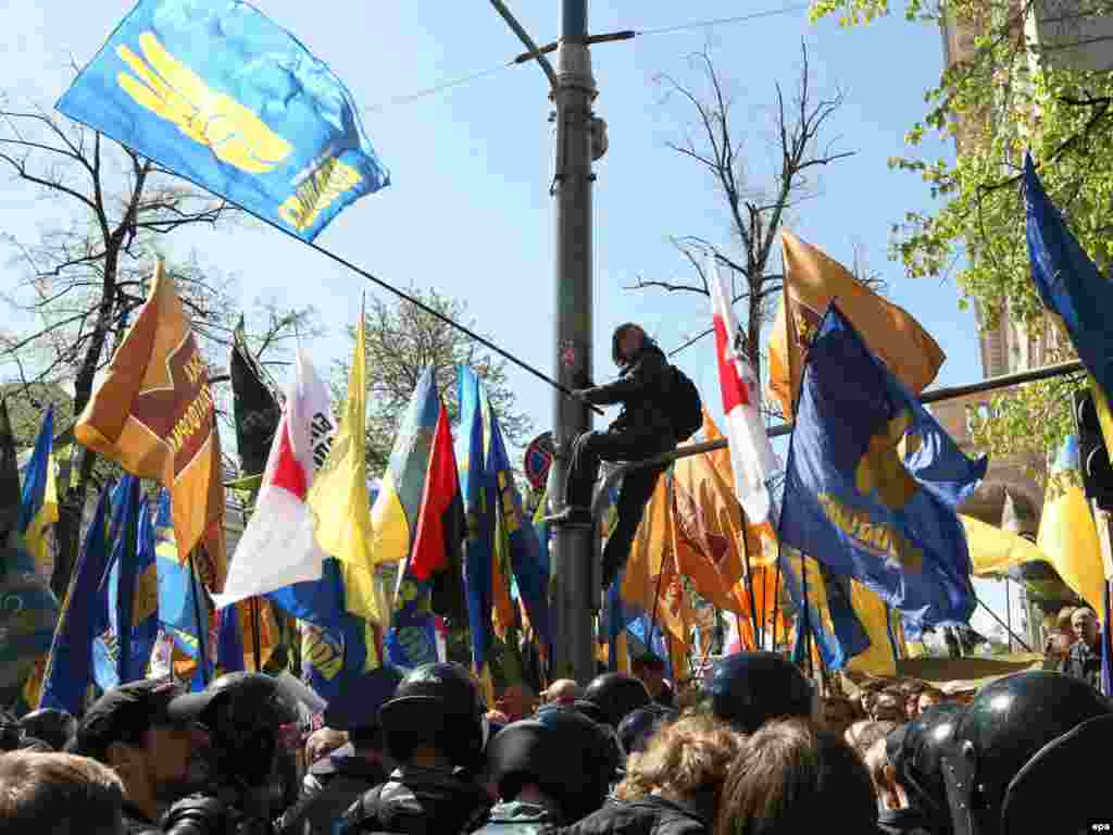 Прихильники опозиції скандують «ганьба!». Вони тримають партійні прапори «Нашої України», ВО «Свобода» та БЮТ.