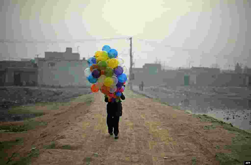 Afghan balloon vendor Arash, 19, waits for customers as he walks through a neighborhood in Kabul. Arash sells balloons for 5 Afghani -- less than one U.S. cent. He says he makes around $4 per day when business is good. (AFP//Shah Marai)