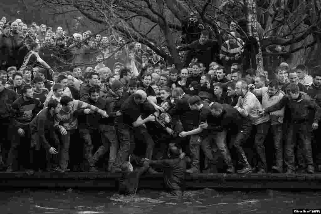 The Up'ards and Down'ards grapple for the ball during the annual Royal Shrovetide Football Match in Ashbourne, in Derbyshire, England. Sports -- First Prize, Singles. (Oliver Scarff, AFP)