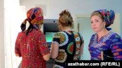 Жительницы Туркменистана снимают деньги с банкомата.