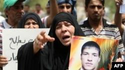 ام تحمل صورة ابنها السجين، ساحة التحرير، بغداد، تموز 2011