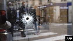 A bullet hole is shown on the window of a cafe located at the crossroads between the streets Saint-Augustin and Monsigny, where a man with a knife killed one man and wounded four other people.