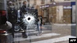 A bullet hole is seen on the window of a Paris cafe, near where Khamzat Azimov was shot dead after going on a knife rampage that killed one person and wounded four others.