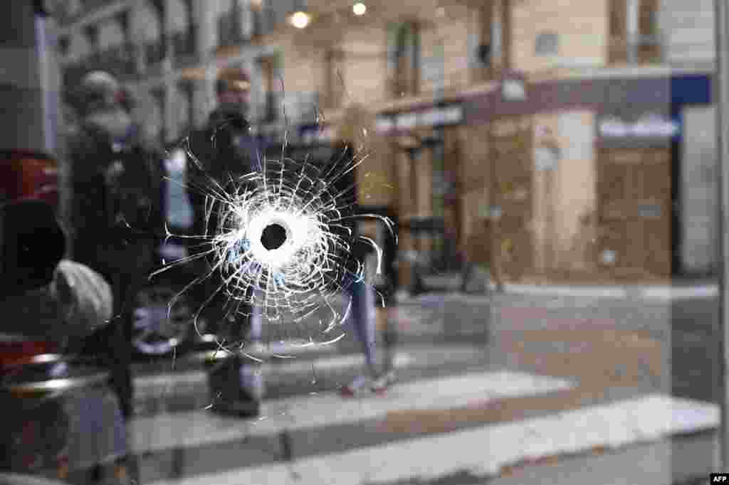 A bullet hole is shown on the window of a cafe located at the crossroads between the streets Saint-Augustin and Monsigny on May 13 in Paris, the day after a knifeman killed one man and wounded four other people. (AFP/Eric Feferberg)