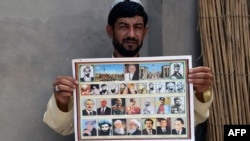 An Afghan man holds a calendar bearing the images of Afghan leaders including the Taliban's late chief Mullah Omar in Kandahar in July 2015.
