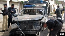 Police inspect the scene of a remote-controlled bomb blast in May 2010 that targeted a police vehicle in Dera Ismail Khan, the site of the most recent attack.