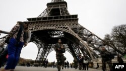 France -- French soldiers patrol the area at the foot of the Eiffel Tower in Paris on November 14, 2015 following a series of coordinated attacks in and around Paris late Friday which left more than 120 people dead. French President Francois Hollande b