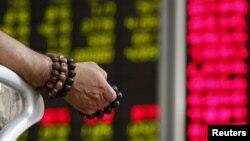 Бээжиндеги брокердик кеңседе баага көз салып отурган инвестор. Кытай, 2015-жыл