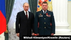 General Lieutenant Valery Asapov (right), then a colonel, stands next to Russian President Vladimir Putin after being decorated by him in a ceremony at the Kremlin in Moscow in February 2013.