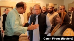 Former Pakistani Prime Minister Nawaz Sharif (center) speaks with members of his former cabinet as he prepares to leave Punjab house in Islamabad on August 9.