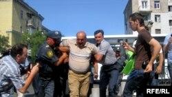 Полиция ведет задержанного участника акции, 3 июля 2010