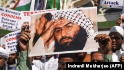 FILE: Indian Muslims hold a scratched photo of Jaish-e Mohammad group chief Masood Azhar, as they protest against Pakistan in Mumbai on February 15.