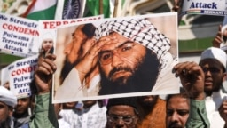 INDIA -- Indian Muslims hold a scratched photo of Jaish-e Mohammad group chief, Maulana Masood Azhar, as they shout slogans against Pakistan during a protest in Mumbai, February 15, 2019
