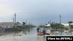 Мужчины на лодке едут по затопленному селу в Мактааральском районе Туркестанской области. 3 мая 2020 года.