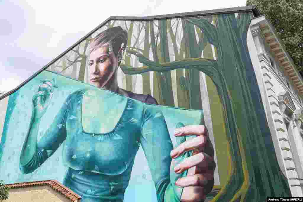 Мурал, изображающий женщину, которая рисует карандашом бумажные самолеты. Созданный командой художников «Sweet Damage Crew»