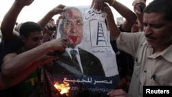 Protesters burn a defaced poster of presidential candidate Ahmed Shafiq, ousted leader Hosni Mubarak's last prime minister, at Cairo's Tahrir Square on June 14.