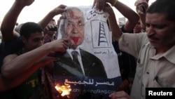Protestçiler Hosni Mubaregiň döwründe hökümete baştutanlyk eden Ahmet Şafigiň portretini ýakýarlar, Kair, 14-nji iýun.