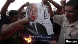 Demonstranti pale plakat sa likom Ahmeda Šafika, Kairo 14.6.2012.