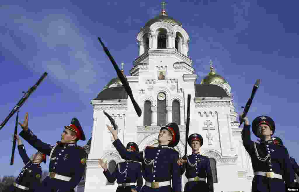 Cossack cadets toss their rifles as they practice for an upcoming performance outside a cathedral in the southern Russian city of Novocherkassk. (Reuters/Vladimir Konstantinov)