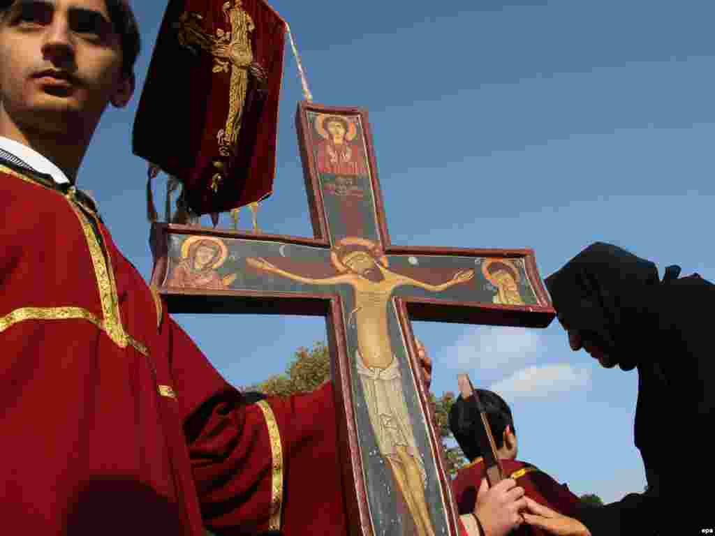 A Georgian boy holds a cross in an annual service in Tbilisi for Georgian Christians who have died for their faith. - Photo by Zurab Kurtsikidze for epa