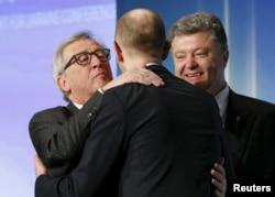 Председатель Европейской комиссии Жан-Клож Юнкер тепло приветствует Арсения Яценюка в присутствии президента Украины Петра Порошенко. Апрель 2015 года