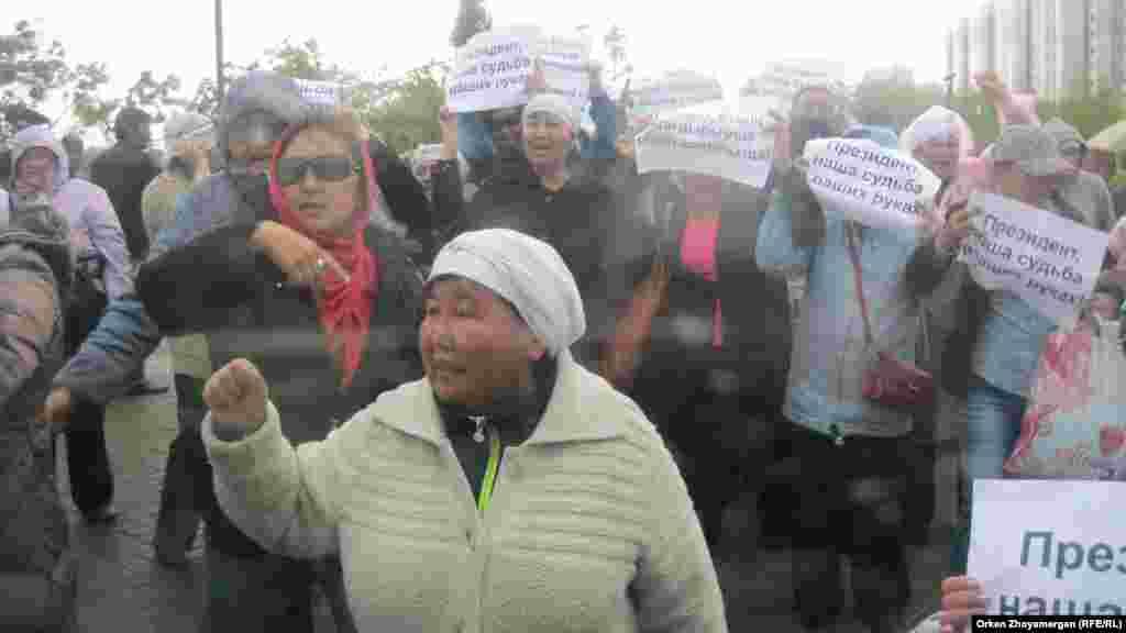 После задержания нескольких людей оставшиеся активисты движения «ипотечников» развернули свои плакатики и начали скандировать лозунги с просьбой к президенту Казахстана Нурсултану Назарбаеву помочь им. Астана, 22 мая 2013 года.