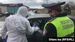 На въезде в Шымкент медработник в защитной одежде замеряет температуру тела водителя автомашины, полицейский проверяет документы. 1 апреля 2020 года.