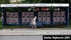 Човек со маска поминува пред предизборни постери во Белград