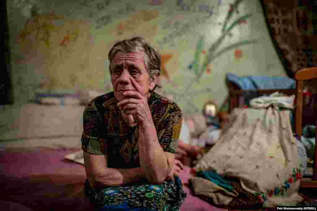Maria, 75, sits on her bed in the shelter.