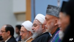 "In this photo released by official website of the office of the Iranian Presidency, President Hassan Rouhani, center, attends an annual Islamic Unity Conference in Tehran, Iran, Saturday, Nov. 24, 2018. Rouhani has called Israel a ""cancerous tumor"" establ"