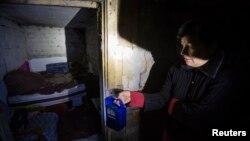 Жінка у підвалі свого будинку, який вона використовує як бомбосховище, 21 жовтня 2014 року