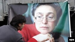 A Russian man lays flowers near the picture of murdered journalist Anna Politkovskaya during a rally in Moscow on the anniversary of her death in 2009.