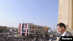 Syrian President Bashar al-Assad greets the crowd during a visit to Raqqa on November 6.