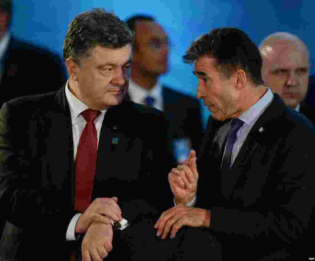 Лидеры стран - членов НАТО на саммите в Уэльсе 5 сентября заявили о поддержке Украины. Они согласовали создание трастовых фондовв поддержку обороноспособности Украины и для нужд военнослужащих украинской армии, получивших ранения в ходе продолжающегося пятый месяц вооружённого противостояния в Донбассе. Лидеры США и стран ЕС заявили, что против Москвы будут объявлены санкции в ответ на значительное увеличение ею за последние дни военной поддержки воюющим на востоке Украины пророссийским сепаратистам. На фото: президент Украины Петр Порошенко и генеральный секретарь НАТО Андрес Фог Расмуссен (справа).