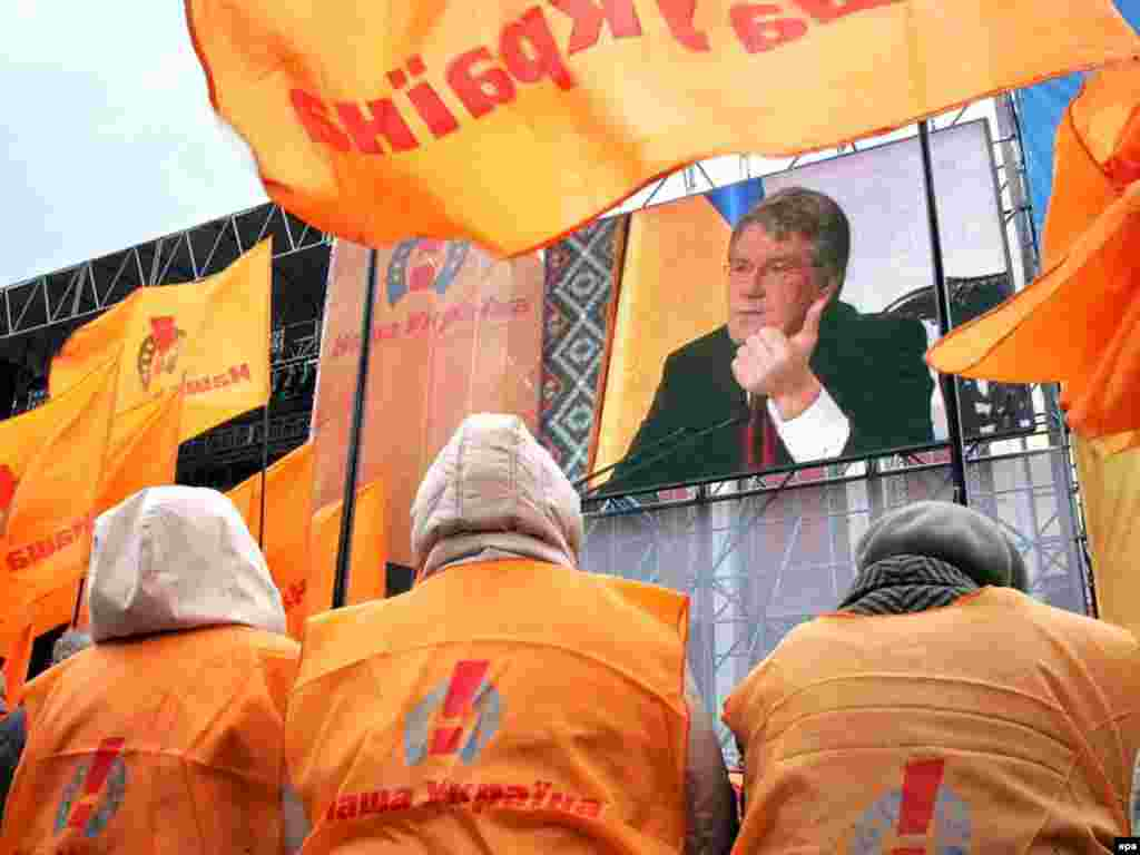 Orange Vs. Blue - Supporters of Ukraine's pro-presidential opposition watch President Viktor Yushchenko speak during a televized news conference on April 12. (photo: epa)