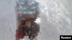 Жінка дивиться через заморожене вікно у маршрутці в Києві, 13 лютого 2012 року температура повітря мінус 19 градусів