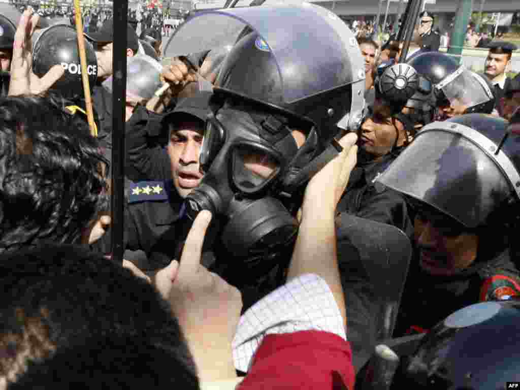 A demonstrator confronts a riot policeman wearing a gas mask after Friday Prayers in Cairo on January 28.