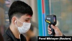 У мужчины в медицинской маске перед входом в один из торговых центров проверяют температуру тела. Алматы, 17 марта 2020 года.