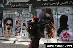 """""""Isten hozott"""" – valószínűleg nem a táliboknak szólt a bezárt szépségszalon üzenete, amely előtt egy tálib harcos halad el, vállán amerikai gépkarabéllyal Kabul Sar-e Nav utcáján 2021. augusztus 18-án"""