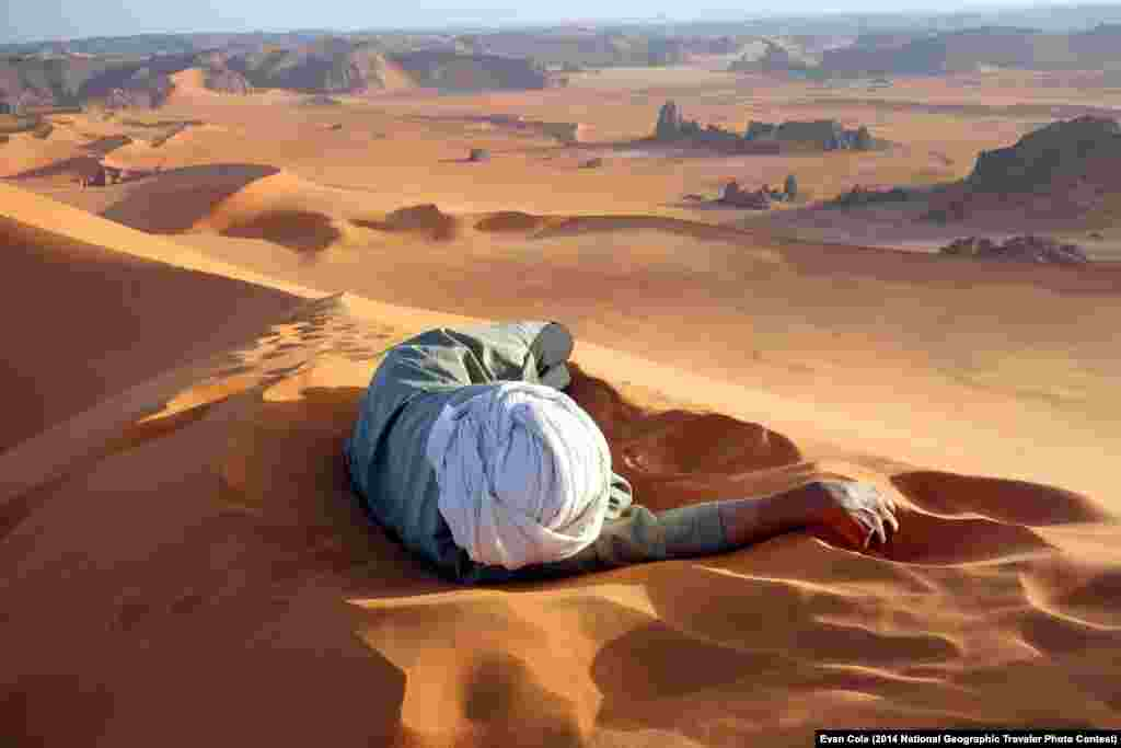"""A well earned rest in the Sahara"" by Evan Cole. Summit of Tin-Merzouga, Tadrat, Tassili N'Ajjer National Park, Algeria. ""This photo, of Moussa Macher, our Touareg guide, was taken at the summit of Tin-Merzouga, the largest dune (or erg) in the Tadrat region of the Sahara desert in southern Algeria. Moussa rested while waiting for us to finish our 45 minute struggle to the top. It only took 10 minutes of rolling, running and jumping to get to get back down. The Tadrat is part of the Tassili N'Ajjer National Park World Heritage Area, famous for its red sand, and engravings and rock paintings of cattle, elephants, giraffes and rhinos that lived there when the climate was milder."""