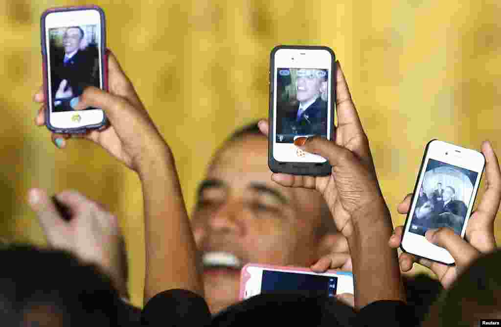 Attendees photograph President Barack Obama with their mobile phones at a Women's History Month reception at the White House in Washington. (Reuters/Jonathan Ernst)