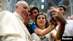 Pope Francis poses with young people during a meeting at the Vatican earlier this year.