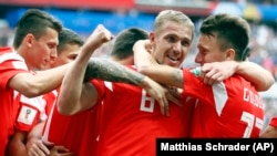 Russia's Yury Gazinsky celebrates with teammates after scoring his side's first goal during the group A match between Russia and Saudi Arabia on June 14 in Moscow. Russia won 5-0.
