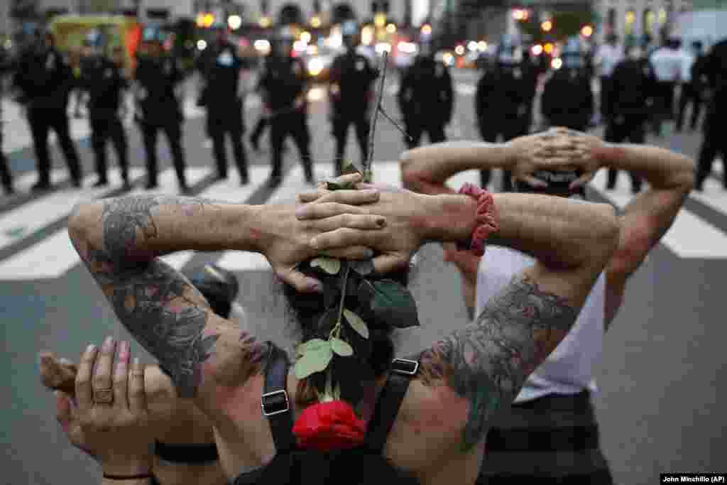 Кілька протестувальників стоять на коліні перед шеренгою поліцейських. Через кілька хвилин поліція затримала їх за порушення комендантської години.Нью-Йорк, неподалік готелюPlaza Hotel на вулиці59th Street. 3 травня 2020 року(Фото AP/John Minchillo)
