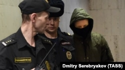 Former Moscow police officer Roman Feofanov (right) arrives for a hearing at Moscow's Basmanny court on January 29.