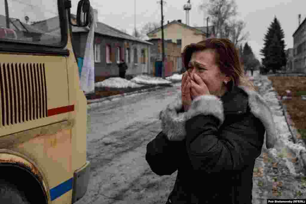 Женщина провожает автобус, на котором вывозят жителей из Дебальцева
