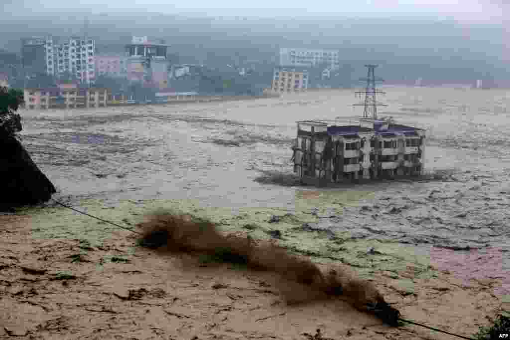 Heavy floodwaters sweep through Beichuan in southwest China's Sichuan Province, as rainstorms sweeping across parts of China have affected millions, causing landslides and disabling transportation. (AFP)